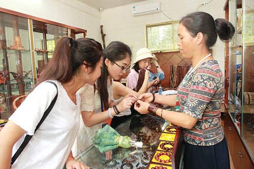 游客挑选购买黄花梨手工艺品