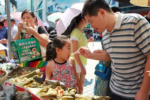 小朋友在活动现场品尝儋州粽子