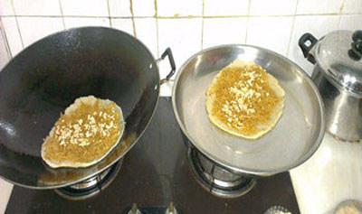 在面饼上均匀地撒椰丝、花生、芝麻